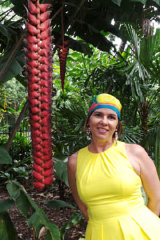 Trudi wears a silk head scvarf as she poses against a giant heliconia flower.
