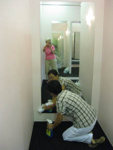 Jill, seen in mirror, photographs Yoshiko painting walls