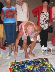 Jack Heywood, performing as Ian Fairweather, uses symbols, line and colour as he paints his canvas on the floor.