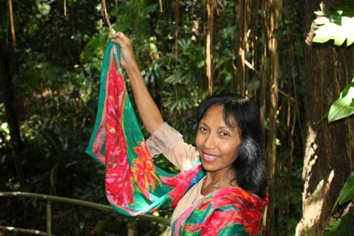 Norlia in the rainforest, her bright silk scarf a splash of colour against the dark greens.