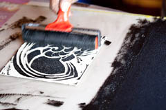 Inking up a lino block ready for printing