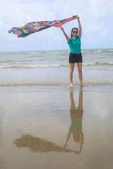 Rosalind with her large silk scarf on a windy day on Four Mile Beach, her shadow reflected in the wet sand.
