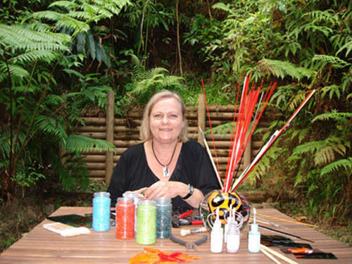 Marie sits in the r ainforest composing her glass jewellery