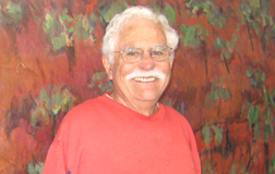 Jim Cobb, his red earth landscape painting in the background.