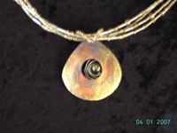 gold and silver coloured coconut pendant with central gemstone