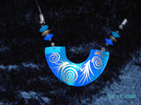 gold spirals on blue painted coconut pendant