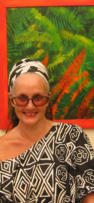 Lnda Jackson wearing one of her own geometric black and white designs, standing in front of her tropical leaves painting