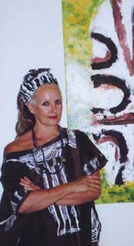 Linda Jackson stands near one of her works hung on wall