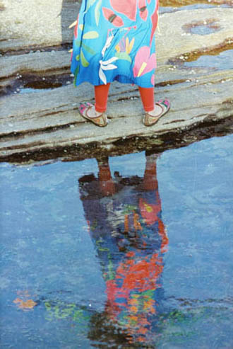 Linda in wildflower appliqued garments, reflected in ocean rock pool