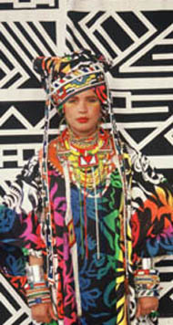 Model wears 'ethnic' outfit with turban hat - strong black and white geometric patterned fabric behind