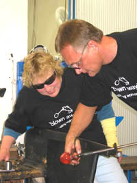 Ola instructs his student in glass blowing