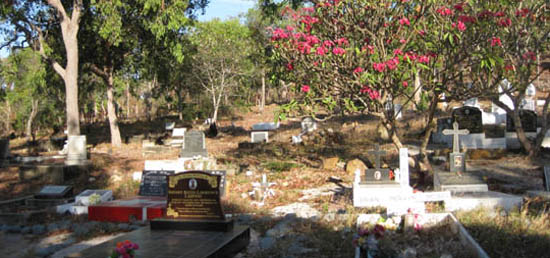 Cemetery on Thursday Island, set in bush with brilliant red frangipani tree in foreground.