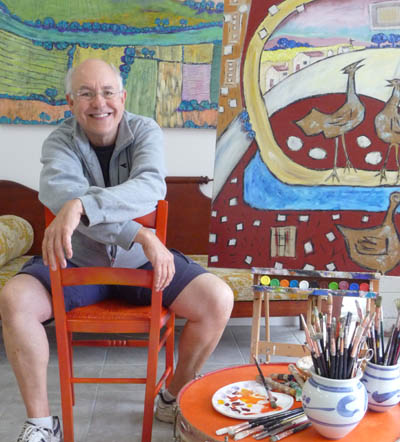 Smiling broadly, Terry sits astride a red chair in his studio, surrounded by paintings.