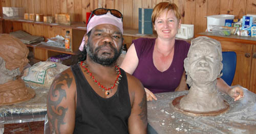 Student works on clay portrait of aboriginal man