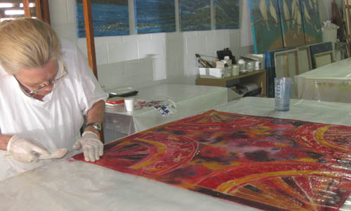 Student finishes process of applying chemical to painted silk scarf