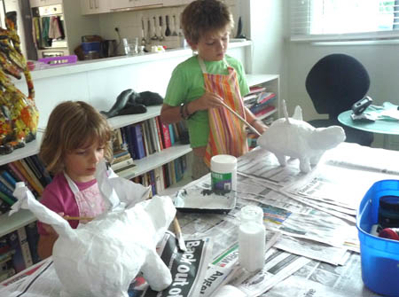Children finish gluing layer of white paper on paper mache sculotures of fantasy animals.