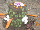 Dirt castle, decorated with tomatoes, green leaves and orange flowers