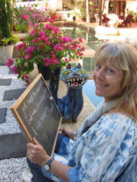 Frieda writes haikus on a small blackboard in her tropical garden