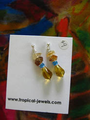 Amber and light blue beaded earrings against a silk scarf in muted colours