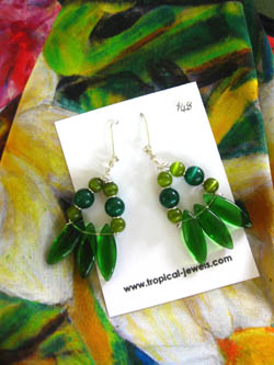 Sterling silver earrings in the form of a triangle with darlk green and light green glass beads on cream frangipani scarf