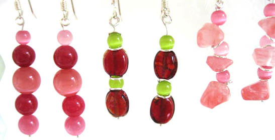 Earrings in deep pinks, lighht pinks and red with green, some with silver rings