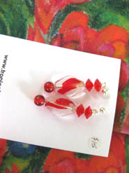 Bright red and clear earrings on a red ginger scarf