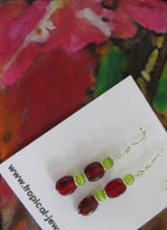 Red and green silver and glass earrings complement the silk scarf on which it sits.