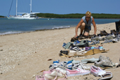 Jill Chism arranges her installation of shoes on the beach at Low Isles