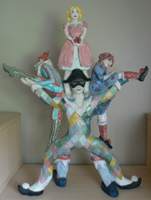 clay sculpture of performers on each other's shoulders