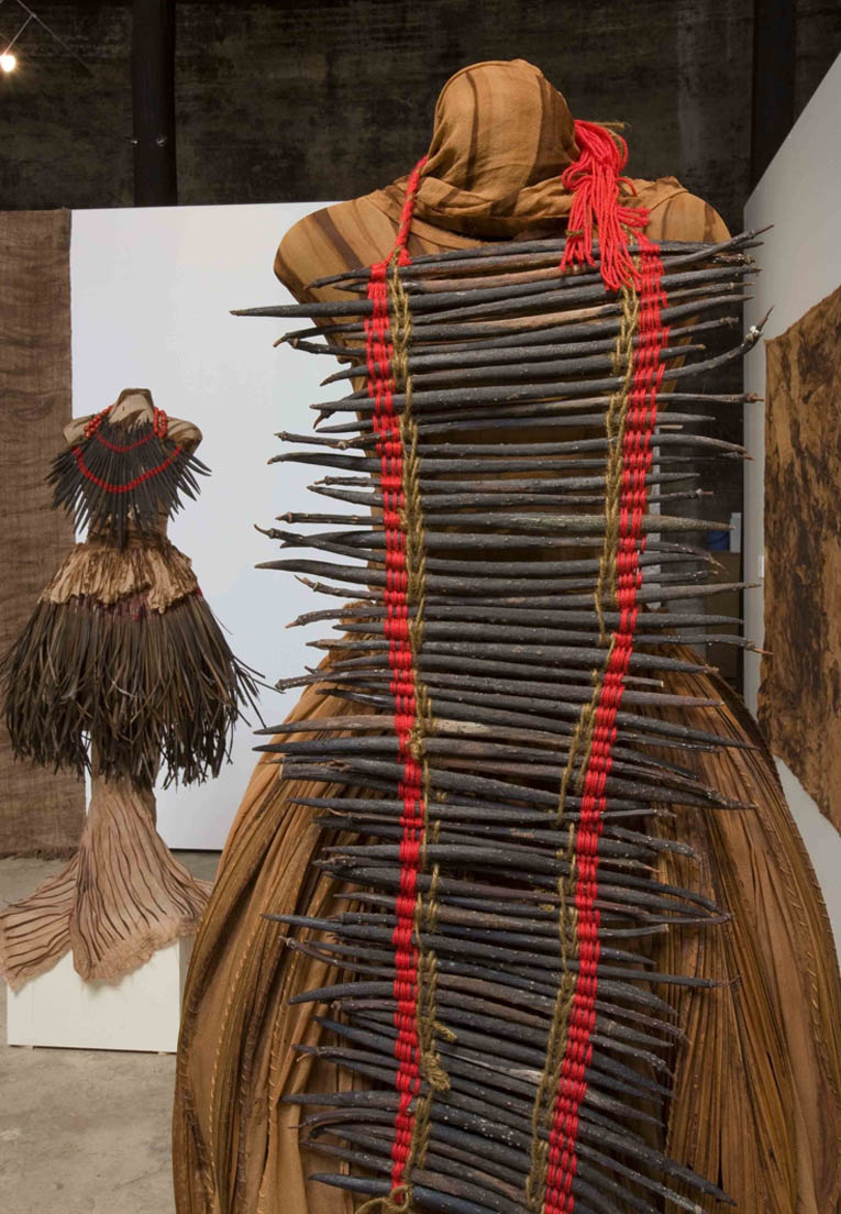 Brown black palm sticks and red threads adorn this mangrove dyed garment made by Linda Jackson