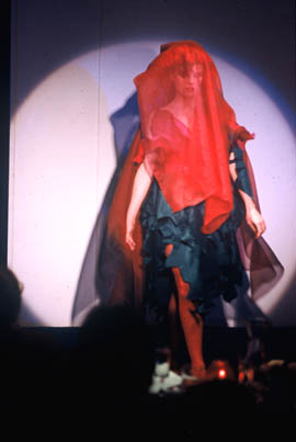 Nell spotlighted in fashion show wearing black waratah dress with sheer red scarf over her head and face