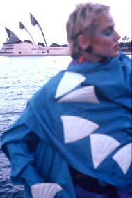 model wears opera house outfit, the actual opera house in the background