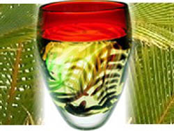 red and green graal glass vase against coconut frond background