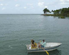 Bridesmaids are rowed to shore in a dinghy