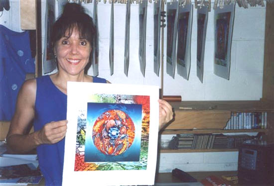 Anna Curtis in her studio, holding one of her linoprints, the drying rack behind.