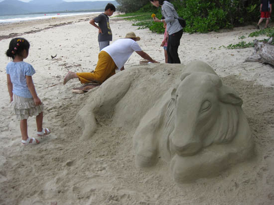 Children interact with interest as Ross works on the Brahman Cow sand sculpture