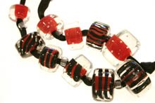 black, red and clear beads threaded on black rope - Marie Hoglund