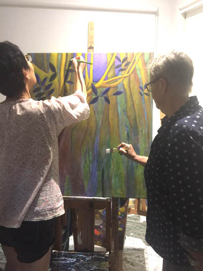 Yoshiko and Joy work on their collaborative painting.