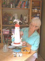 Judy Richards works on her sculpture of Low Isles volunteers in their stinger suits, grouped around the lighthouse.