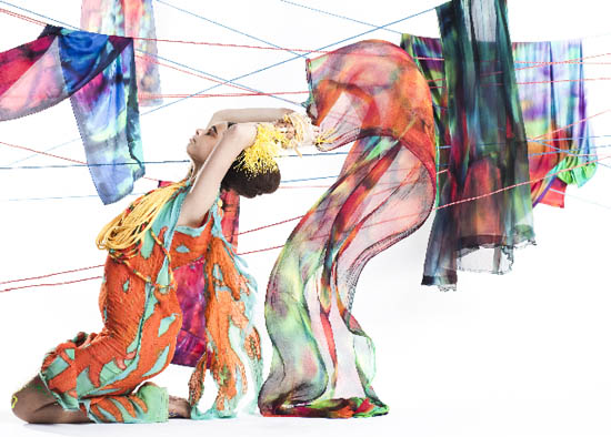 'Opal' silk long scarves in bright strong colours, strung over lines and blowing in the breeze, model tossing her arms backwards to increase the effect of abandonment