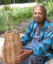 Wilma, aboriginal weaver holds one of her large baskets
